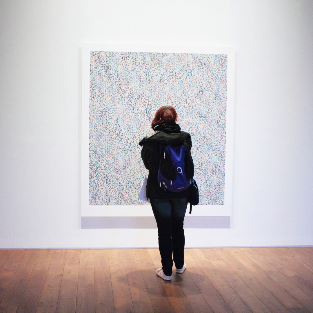A museum visitor standing in front of a painting.