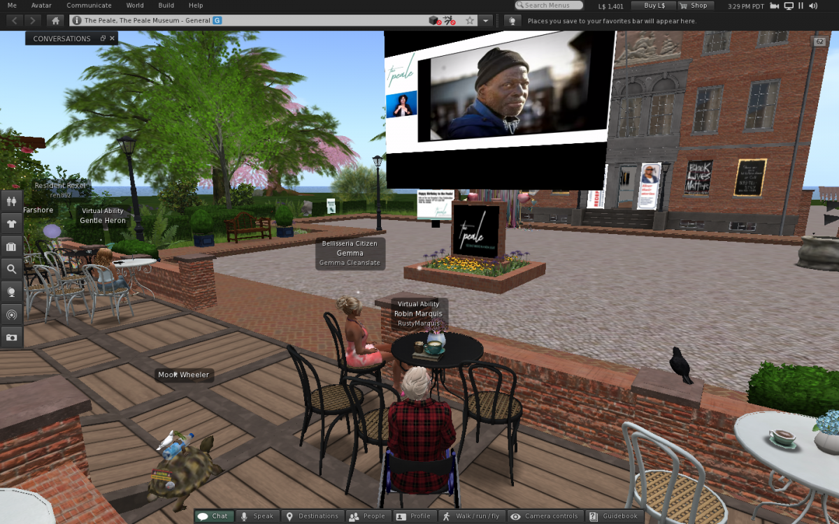 A screen shot of The Peale's brick building in the virtual world Second Life during the recent Founders Day Celebration. The avatar of Robin Marquis sits in a wheel chair with others on a patio watching the live event on a projector screen.